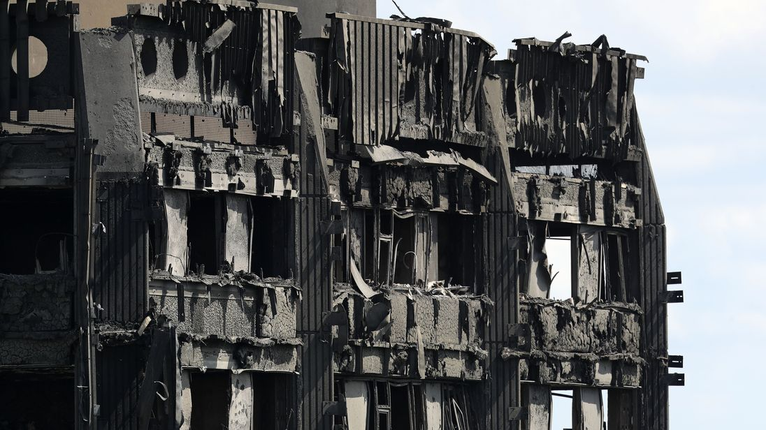 Debris hangs from the blackened exterior of Grenfell Tower