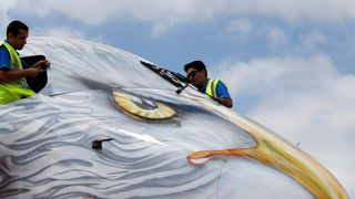 Two workers cover the cockpit of an Embraer E190-E2, on the static display, before the opening of the 52nd Paris Air Show at Le Bourget airport near Paris, France June 17, 2017. REUTERS/Pascal Rossignol