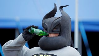 A man dressed as Batman drinks beer