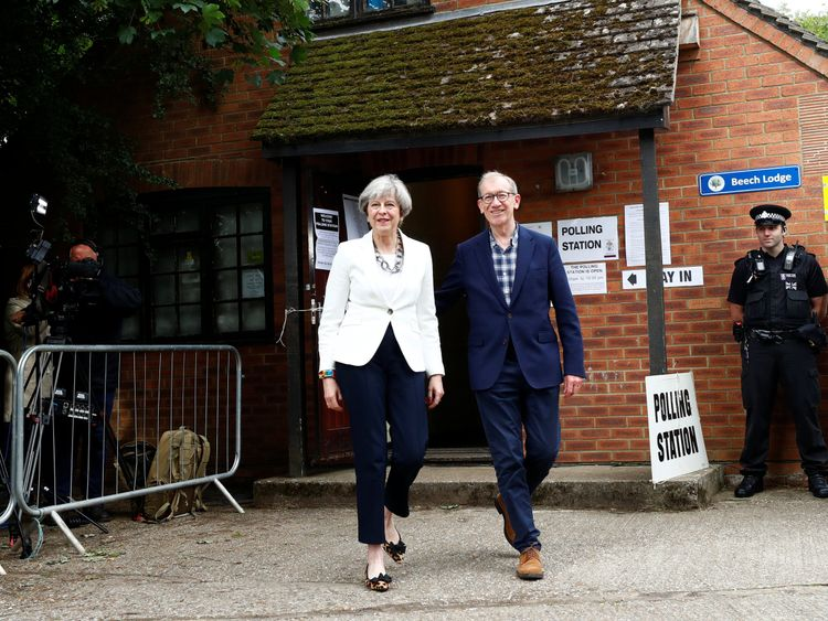 Theresa May and her husband Philip leave a polling station in Sonning