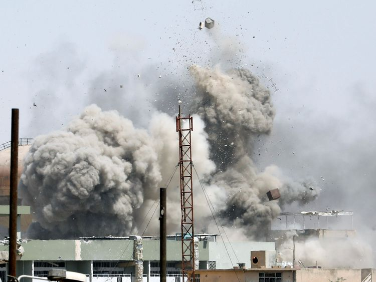 Debris fly as smoke rises after an artillery attack on the Islamic State militants' positions