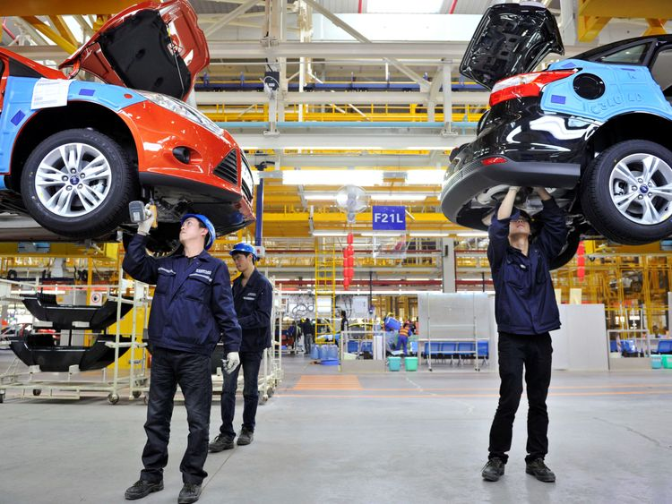 Employees install car components at an assembly line at a Ford manufacturing plant in China