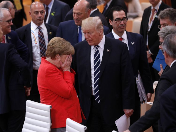 German Chancellor Angela Merkel reacts next to US President Donald Trump