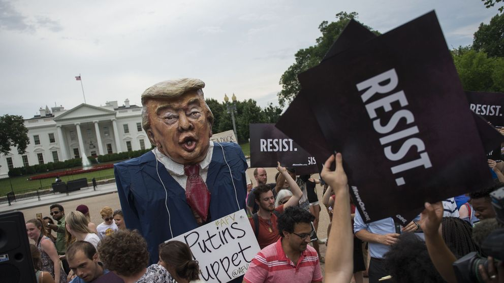 Protesters brand Mr Trump 'Putin's puppet' during a protest outside the White House