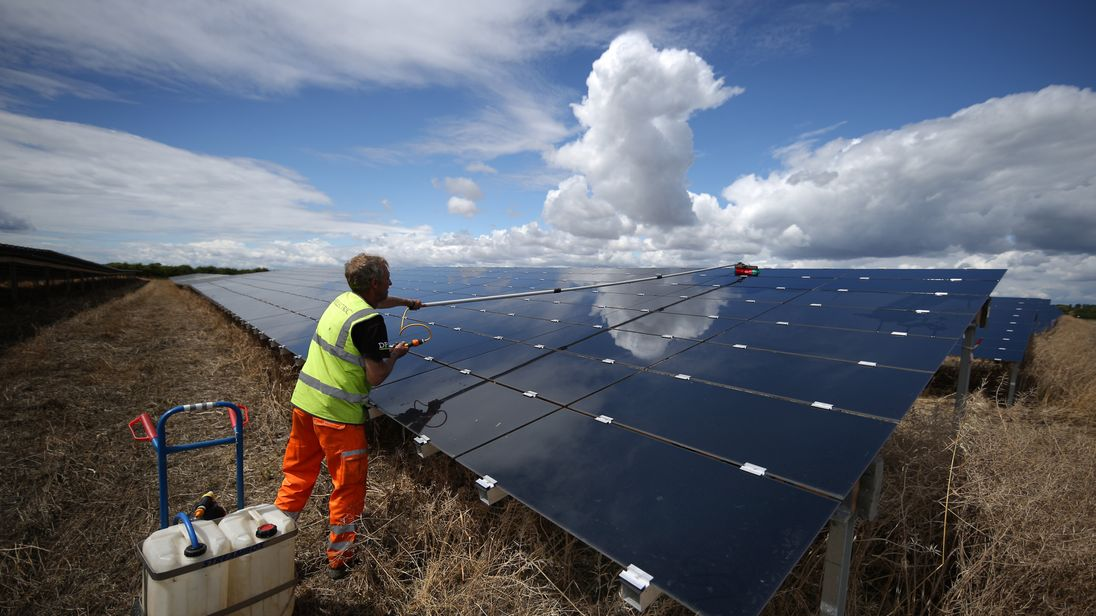 A workman cleans panels at Landmead solar farm on July 29, 2015 near Abingdon, England