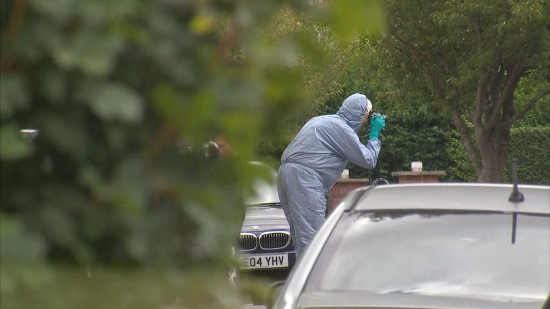 Forensic officers inspect the crime scene