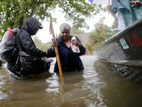 A man helps his neighbour get onto a rescue boat in Houston