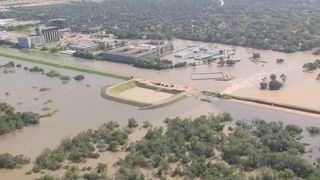 An aerial view of a dam in Houston, surrounded by flood waters