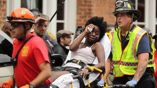 Rescue workers move victims on stretchers after car plowed through a crowd of counter-demonstrators