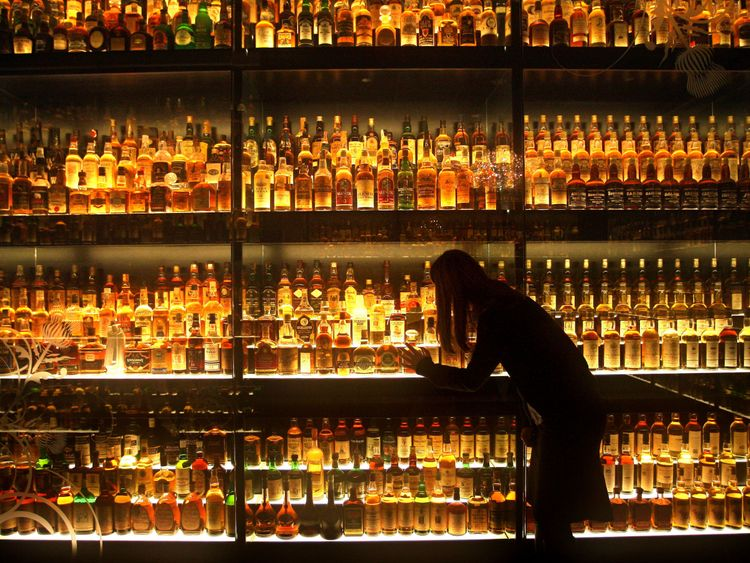 A member of staff looking at the Diageo Claive Scotch Whisky collection