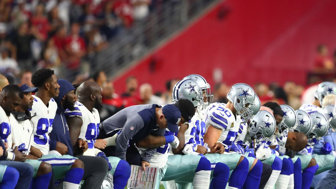 Dallas Cowboys players kneel together with their arms locked prior to the game against the Arizona Cardinals. Mandatory Credit: Mark J. Rebilas-USA TODAY Sports
