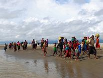 Rohingya refugees walk on the shore after crossing the Bangladesh-Myanmar border by boat through the Bay of Bengal