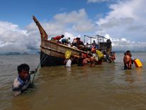 Rohingya refugees get off a boat after crossing the Bangladesh-Myanmar border through the Bay of Bengal