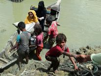 Local Bangladeshis help Rohingya Muslim refugees to disembark from a boat on the Bangladeshi side of Naf river near the Bangladeshi town of Teknaf