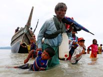 A Rohingya refugee man pulls a child to the shore after crossing the Bangladesh-Myanmar border by boat through the Bay of Bengal in Shah Porir Dwip