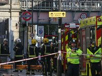 Members of the emergency services work outside Parsons Green station after the attack