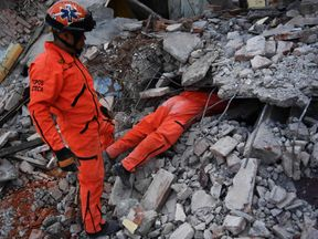 Member of the Moles specialised rescue team search for survivors in Juchitan de Zaragoza