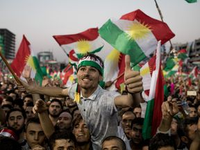 Supporters wave flags and chant slogans inside the Erbil Stadium while waiting to hear Kurdish President Masoud Barzani