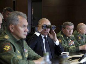 Russian President Vladimir Putin uses a pair of binoculars while watching the Zapad-2017 war games
