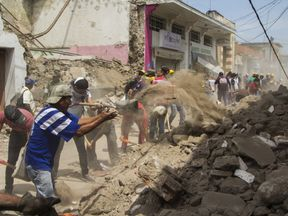 Volunteers clean the debris from damaged houses in Jojutla de Juarez on September 20, 2017 a day after a strong quake hit central Mexico