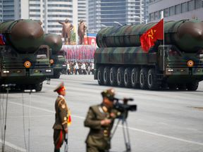 FILE PHOTO: Intercontinental ballistic missiles (ICBM) are driven past the stand with North Korean leader Kim Jong Un and other high ranking officials during a military parade marking the 105th birth anniversary of country's founding father Kim Il Sung, in Pyongyang April 15, 2017. The missiles themselves were shown for the first time inside a new kind of canister-based launcher on Saturday