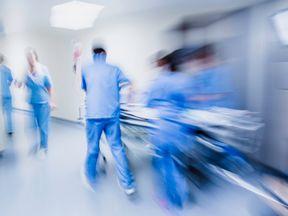NHS staff push a bed down a hospital corridor