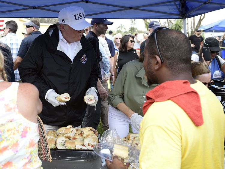 US President Donald Trump helps serve food to people affected by Hurricane Irma, in Naples, Florida, on September 14, 2017. / AFP PHOTO / Brendan Smialowski (Photo credit should read BRENDAN SMIALOWSKI/AFP/Getty Images)