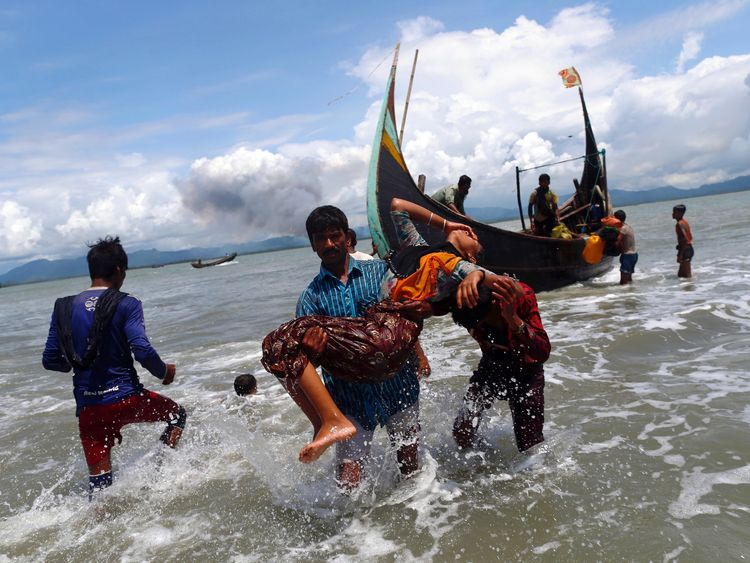 An exhausted Rohingya refugee woman is carried to the shore after crossing the Bangladesh-Myanmar border by boat through the Bay of Bengal