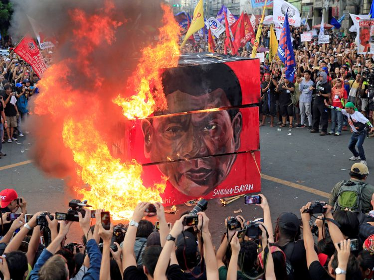 Protesters burn a cube effigy with a face of President Rodrigo Duterte during a National Day of Protest in metro Manila, Philippines