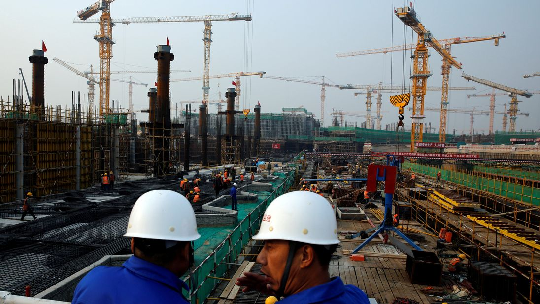 FILE PHOTO: Workers survey the construction site of the terminal for the Beijing New Airport in Beijing's southern Daxing District, China October 10, 2016.