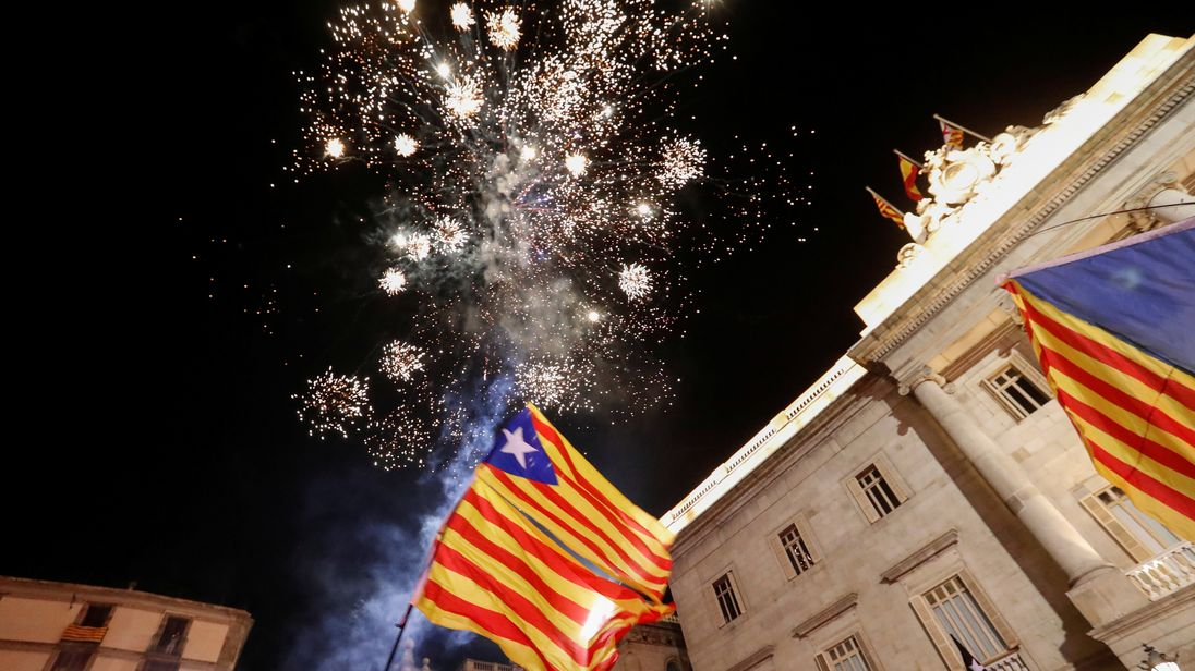 Catalan separatist flags are held up as fireworks go off in Sant Jaume Square