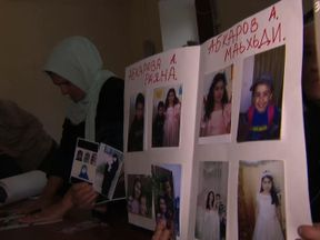 Chechen mothers hold photographs of their missing family after they married IS fighters