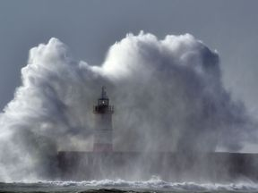 Waves crash over Newhaven Lighthouse in East Sussex
