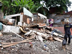 A man and a dog walk amid the rubble after Tropical Storm Nate struck Costa Rica
