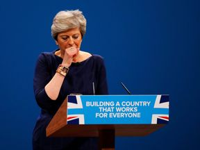 Britain's Prime Minister Theresa May coughs as she addresses the Conservative Party conference in Manchester