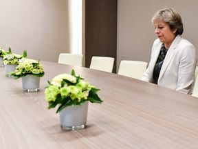 British Prime Minister Theresa May takes a seat as she arrives for a bilateral meeting with European Council President Donald Tusk in Brussels