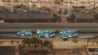 Pacific Gas and Electric (PG&E) trucks are seen parked on a road between homes destroyed by the Tubbs Fire in Santa Rosa, California