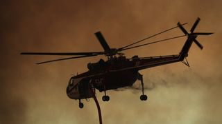 A firefighting helicopter flies in to make a water drop on a wind driven wildfire in Orange, California
