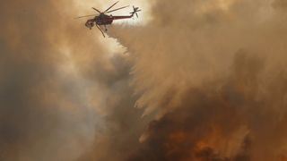A helicopter drops water on a wind driven wildfire in Orange, California