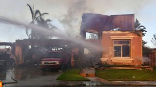 Firefighters water down a house destroyed by a the fire in the Anaheim Hills neighbourhood in Anaheim, California