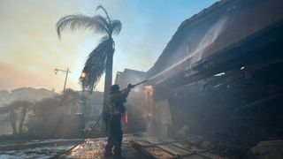 A fireman puts out a fire at a home in the Anaheim Hills neighbourhood in Anaheim, California
