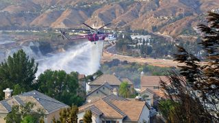 A helicopter drops water near homes at the Anaheim Hills neighbourhood in Anaheim, California