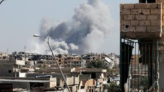 Smoke rises near the stadium where the Islamic State militants are holed up after an air strike