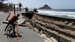 An exposed crater along the boardwalk of Macumba beach after waves washed away the sand in the weekend storm, in Rio de Janeiro, Brazil
