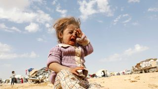 A girl cries at a refugee camp for people displaced in fighting between the Syrian Democratic Forces and Islamic State militants in Ain Issa, Syria
