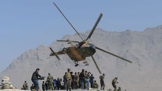 An Afghan Air Force Mi-17 helicopter flies past commandos during a military exercise at the Kabul Military Training Centre