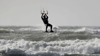 """A kitesurfer off West Wittering beach in West Sussex, as a """"weather bomb"""" is set to bring heavy wind and rain to the UK"""