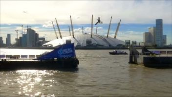 Action sports performer backflips motorbike between Thames barges
