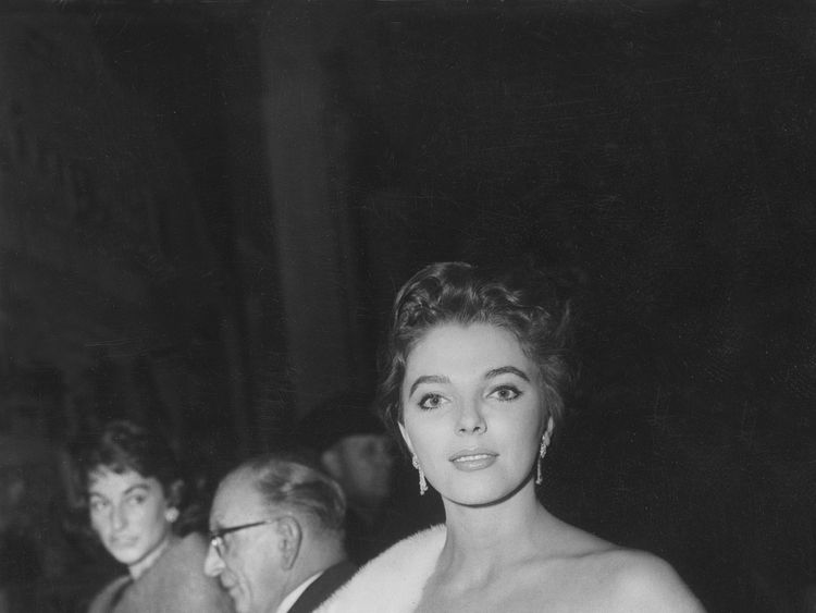 2th September 1956: Joan Collins arrives at the European premiere of 'The King & I', wearing an evening gown and white fur stole. (Photo by Keystone/Getty Images)