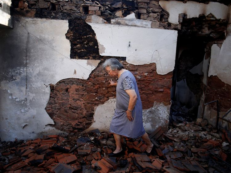 Albertina Miranda walks inside her burnt house after a forest fire in Lagares, near Santa Comba Dao, Portugal October 17, 2017